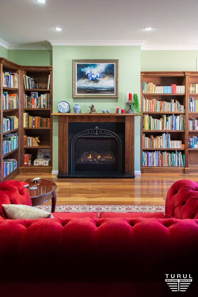 Burpengary Private Library Couch with Bookshelves next to a Fireplace - Narrow View