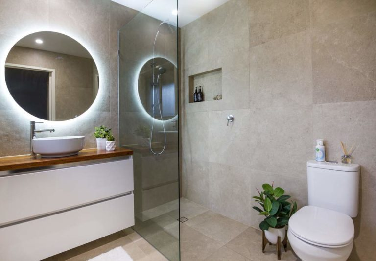 Bathroom renovated in a modern stile with dark tiles, glass shower cabin and round mirror