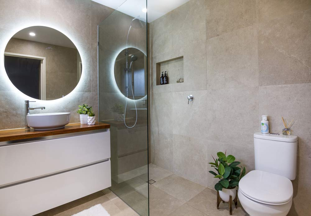Batroom renovations Brisbane wide with Turul: bathroom renovated in a modern stile with dark tiles, glass shower cabin and round mirror