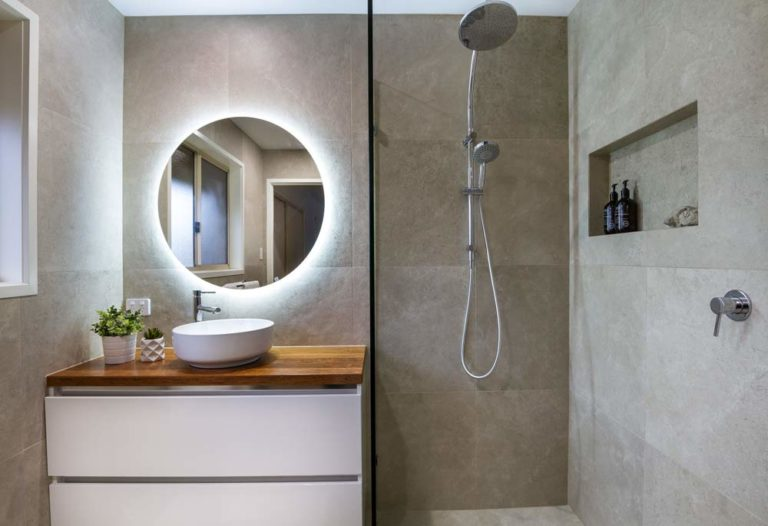 Bathroom renovation completed by Turul Building Services - A modern bathroom with large dark tiles, round backlit mirror, a half-open shower cabin with dual shower head in two sizes