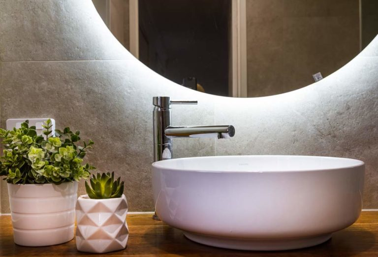 A modern vanity with an elegant hand basin and a round mirror
