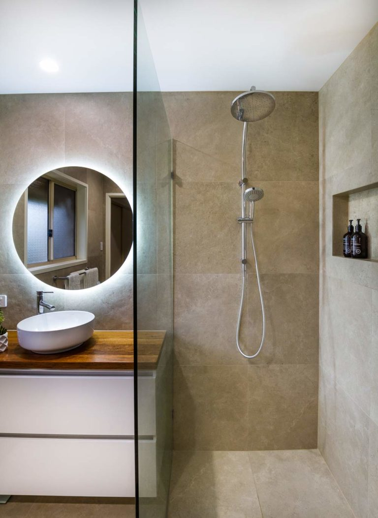 A modern half-open shower cabin separated from the bathroom by a glass panel, large dark tiles and a dual shower head | Recent bathroom renovation by Turul Building Services
