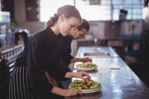 Restaurant staff prepare salad on a commercial kitchen island.