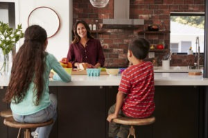 Kids eat breakfast while mother prepares school lunch on a kitchen island.